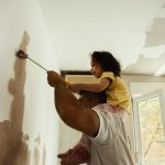 June is National Homeownership Month - Young family renovating their home and painting